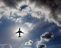 Airplane in the sky. Silhouette of an airplane flying across a blue cloudy sky against a bright shinning sun Stock Photo