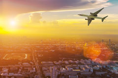 Airplane in the sky above city at sunset. Amazing trip. Travel c Royalty Free Stock Photography