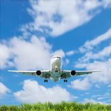 Airplane in the sky with beautiful green grass blue sky scenery Stock Image