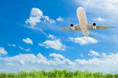 Airplane in the sky with beautiful green grass blue sky scenery Stock Photos