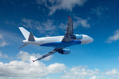 Airplane in the sky. Blue sky with cumulus clouds Stock Photography