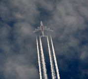 Airplane in the sky. With clouds leaving vapor trails Royalty Free Stock Photo