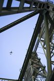 The plane flies over the triangular frames of the lifting bridge Stock Photography