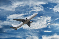Airplane on sky with fluffy and spindrift clouds Royalty Free Stock Photo