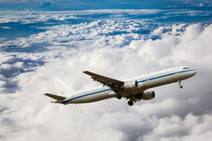 Airplane in the sky full of fluffy clouds Stock Photography