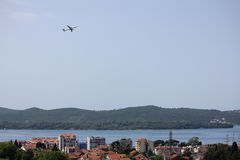 Airplane in the sky over Tivat Stock Photography