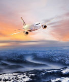 Airplane in the sky over winter Alps at amazing colorful sunset. Airplane in the sky over winter Alps at colorful sunset Royalty Free Stock Images