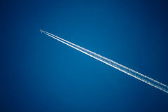Airplane in the sky with plane trails Stock Photography