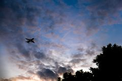 Airplane in the sky, silhouette of a big airliner. Over blue overcast sky background, luxury travel and journey, expensive transport Stock Photos