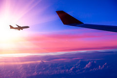 Airplane in the sky at sunrise.  Royalty Free Stock Image