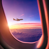 Airplane in the sky at sunrise Stock Photos