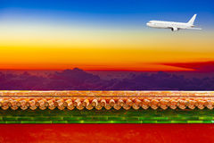 Airplane in sky at sunrise over red walls, meaning China and Eas Royalty Free Stock Photo