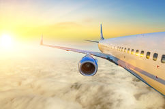 Airplane in the sky at sunrise view of the wing and engine Stock Images