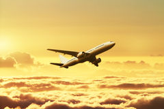 Airplane in the sky at sunset Stock Photography