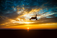 Airplane in the sky at sunset Royalty Free Stock Image