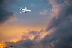 Airplane  in the sky at sunset. Airplane flying in the sky at sunset Royalty Free Stock Photo