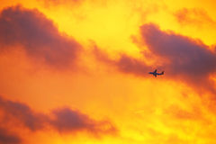 Airplane in the sky at sunset Royalty Free Stock Photos