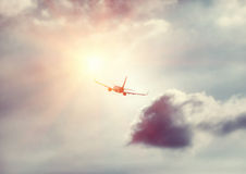 Airplane in the sky. Travel background, silhouette of an airplane in the sky flies towards sun light, modern fast aircraft over cloudy and sunny skies, luxury stock images
