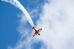 Airplane. A small propeller airplane in blue and yellow on a flight show flying in the air Royalty Free Stock Image