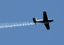 Airplane with smoke trail Stock Photography
