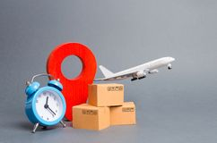 Airplane and stack of cardboard boxes, red position pin and blue alarm clock. concept of air cargo and parcels, airmail. Fast. Delivery of goods and products royalty free stock photography