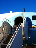 Airplane stairs. Leading up to open door of DC-4 airliner Royalty Free Stock Images