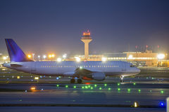 An airplane starting at an airport at night Stock Photo