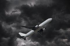 Airplane on stormy sky Stock Photos