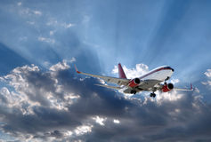 Airplane and sun behind. A plane above Sun rays going through dark clouds royalty free stock photography