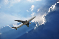Airplane and Sun lights an edge of cloud Royalty Free Stock Images