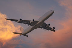 Airplane at sundown in the sky Royalty Free Stock Photo