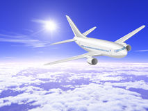 Airplane is in the sunny sky above the clouds. Plane is flying in blue sunny sky over the thick clouds Royalty Free Stock Image