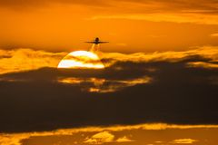 Airplane in sunrise Stock Photos