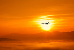 Airplane at sunset with low clouds Royalty Free Stock Image