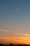 An airplane at sunset over a city Royalty Free Stock Photo
