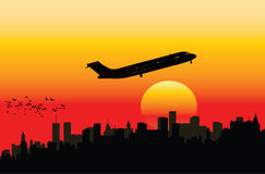 Airplane on sunset sky. Airplane fly in the sunset in a town Stock Photography