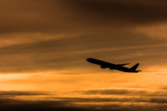 Airplane in the sunset sky, silhouette photo Royalty Free Stock Photos