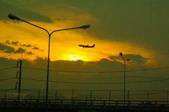 The airplane on the sunsets background Stock Photo