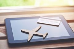 Airplane symbol with credit card and tablet computer stock image