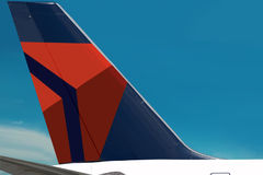 Delta Air Lines logo plain. Sky. Airplane with the symbol (logo) of Delta Air Lines company on the tail is close-up. Beautiful blue sky area is free for your Royalty Free Stock Photography