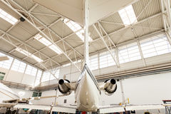 Airplane Tail Inside Brightly Lit Hangar. Low Angle View of Small Passenger Airplane Tail Inside Brightly Lit Hangar with Skylights Royalty Free Stock Photo
