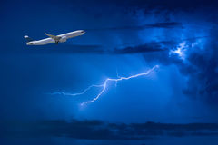 Airplane take off flying over storm clouds and lightning Royalty Free Stock Photo