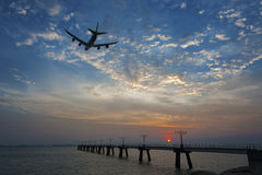 Airplane take off. Passenger plane fly up over take-off runway from airport at suns Stock Image