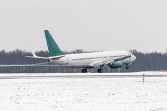 Airplane take off from the snow-covered runway airport in bad weather during a snow storm, a strong wind in the winter. Royalty Free Stock Image