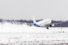 Airplane take off from the snow-covered runway airport in bad weather during a snow storm, a strong wind in the winter. Stock Image