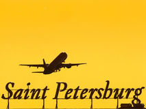 Airplane on takeoff flies above the inscription of the city of St. Petersburg at sunset Royalty Free Stock Image