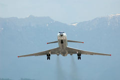 Airplane at takeoff on mountain background Stock Photo