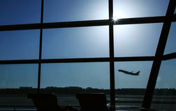 Airplane takes off. An airplane is taking off behind the airport window stock images