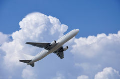 Airplane is takinf off under fluffy clouds in the sky Stock Photos