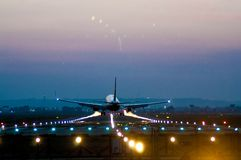 Airplane taking off at an airport at night royalty free stock photography